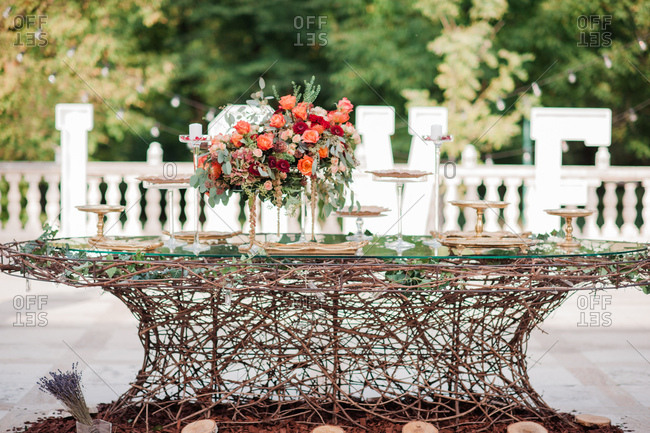 Floral arrangements on table with empty serving trays at outdoor wedding reception
