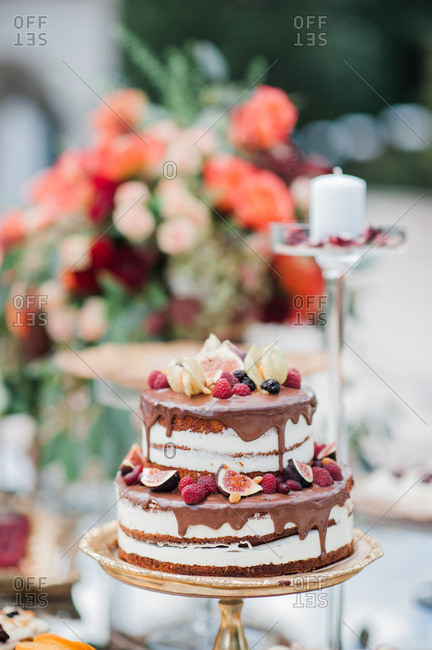 Wedding cake with chocolate icing topped with fruits and berries