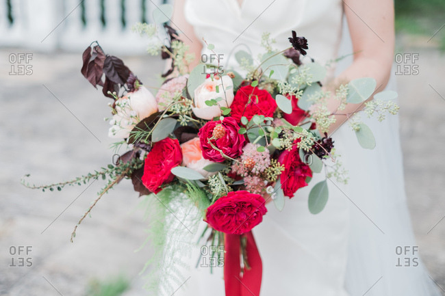 Close-up of bride holding wedding bouquet with red flowers