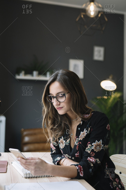 Woman sitting at desk looking at cell phone