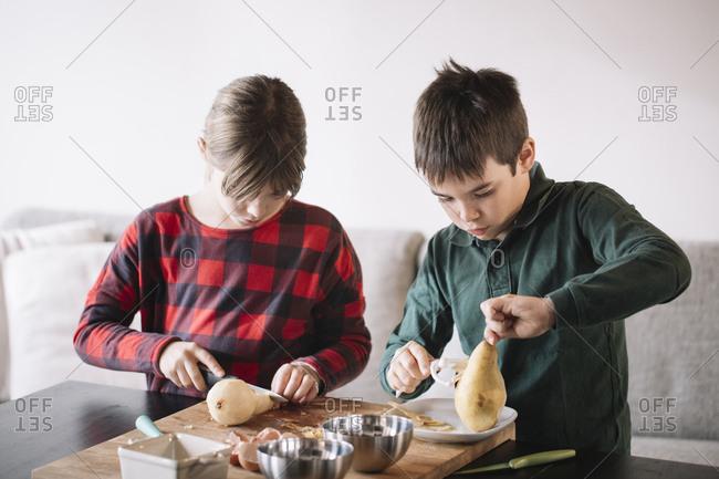 Girl and boy preparing pears
