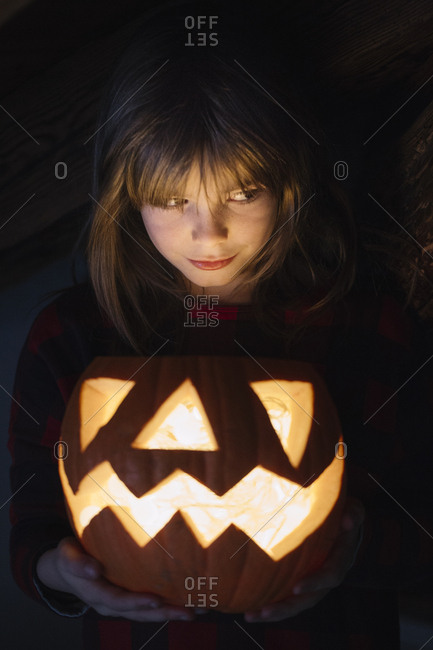 Portrait of girl with lighted Jack O\'Lantern at Halloween