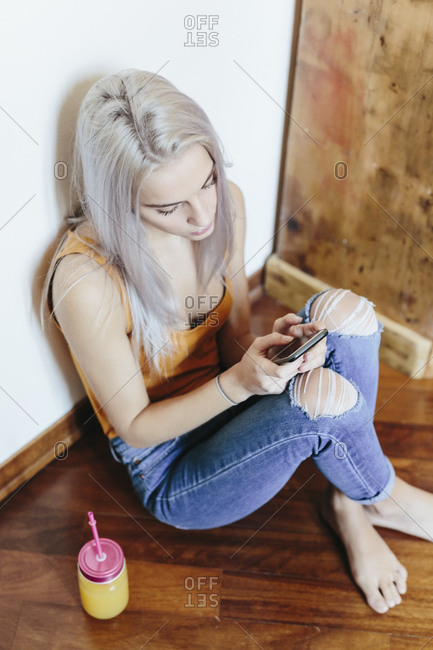 Young woman sitting on the floor at home using smartphone