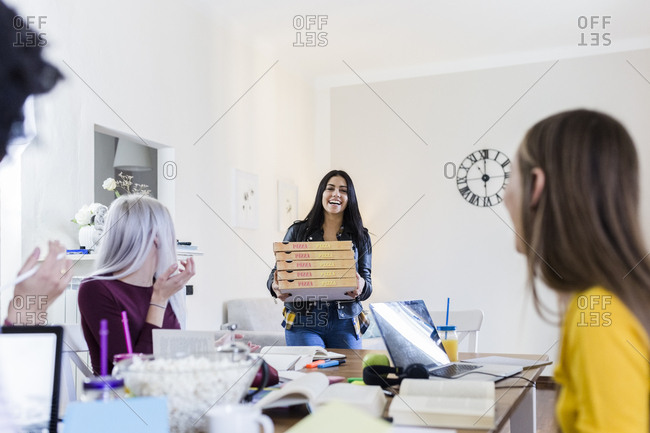 Young women bringing pizza for friends studying at home