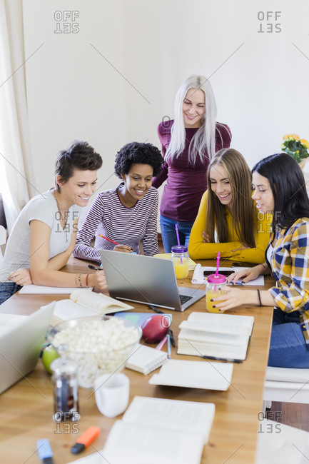Group of female students sharing laptop at table at home