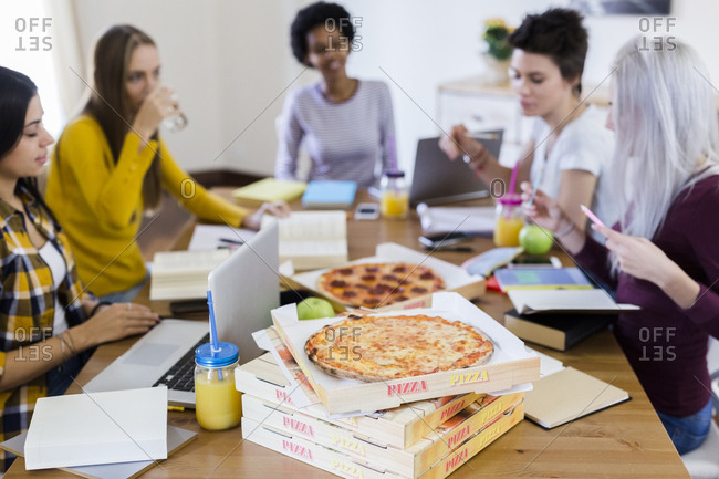 Group of young women at home studying and having pizza