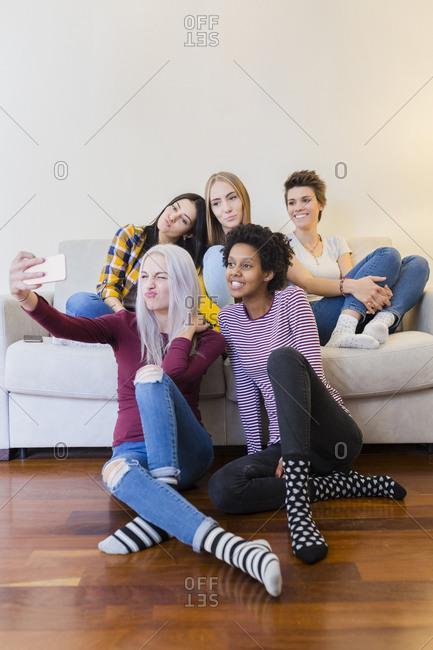 Happy female friends taking a selfie in living room