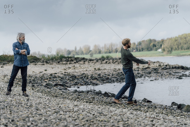 Father and son spending time together- son skipping pebbles