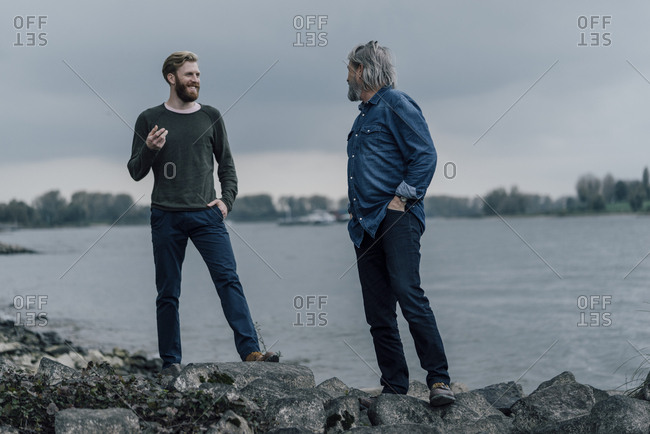 Father and son meeting at Rhine river in autumn- talking together