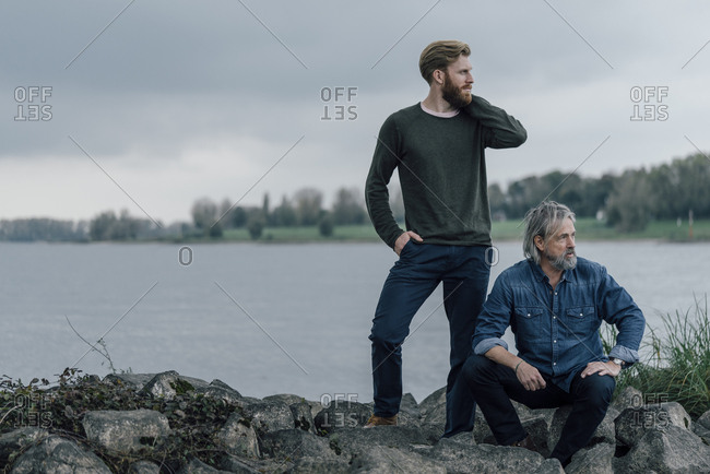 Father and son spending time together outdoors- taking a break- sitting on stones