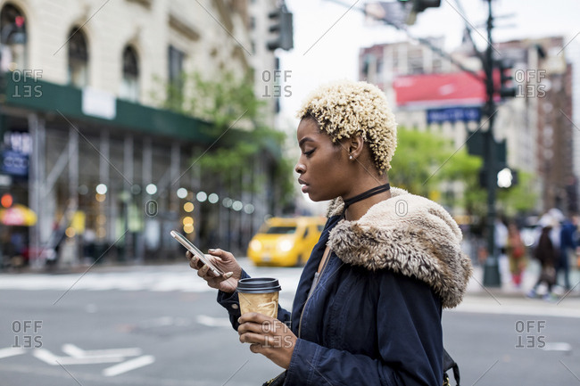 USA- New York City- fashionable young woman with coffee to go looking at cell phone on the street