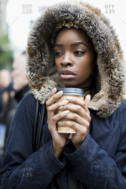 Portrait of fashionable young woman with coffee to go wearing hooded jacket
