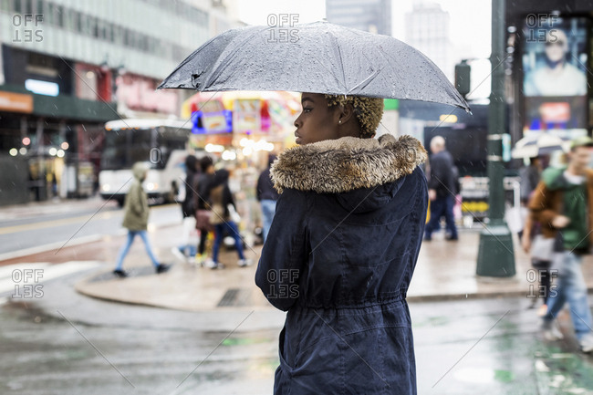 USA- New York City- young woman with umbrella on rainy day