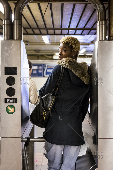 USA- New York City- young woman passing through barrier in subway station