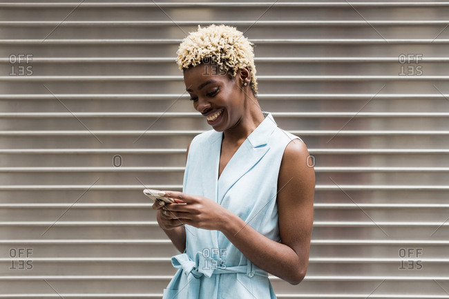 USA- New York- young blonde african-american woman using smartphone- smiling