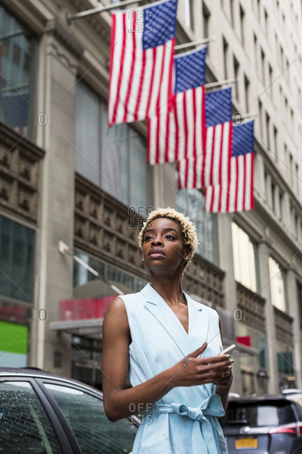 USA- New York- young blonde african-american woman with smartphone