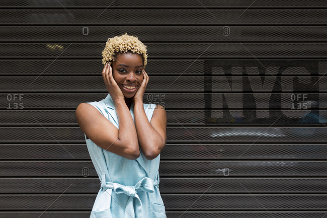 USA- New York- happy young blonde african-american woman- smiling- hand on head