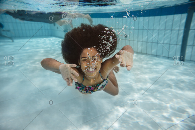 Girl swimming under water in swimming pool