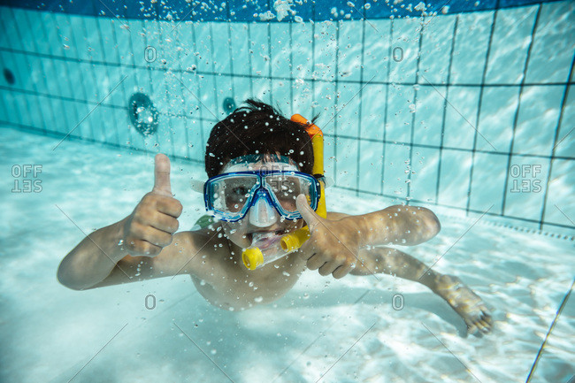Boy with diving goggles and snorkel under water in swimming pool