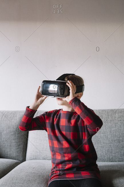 Girl sitting on the couch in the living room using Virtual Reality Glasses