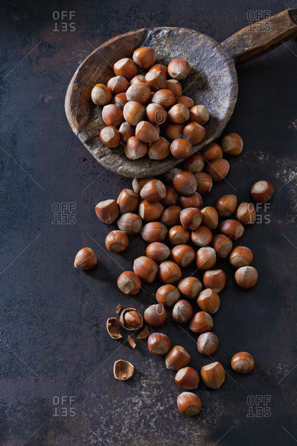Whole and cracked hazelnuts on dark ground