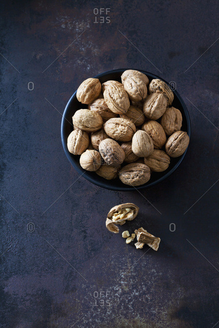 Bowl of walnuts on dark metal