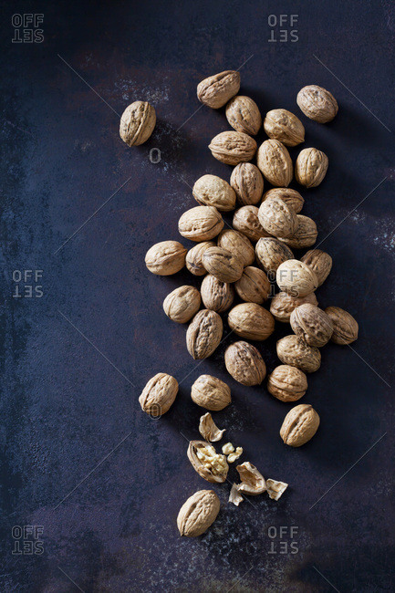 Whole and cracked walnuts on dark metal
