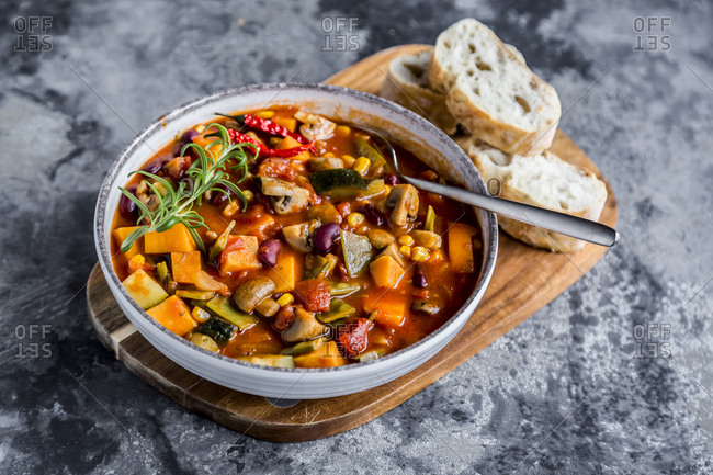 Vegetable chili with kidney bean- sweet potatoes- champignon- corn- snow pea- baguette in bowl