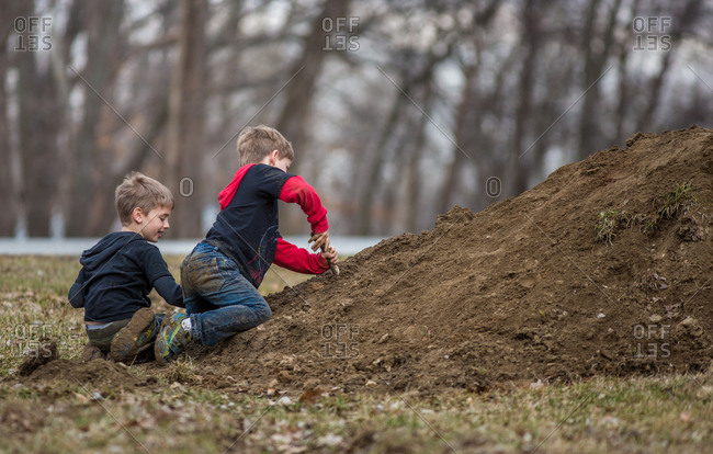 Boys playing outside on pile of dirt