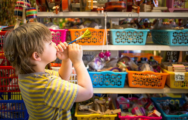 Small boy blowing toy horn in trinket store