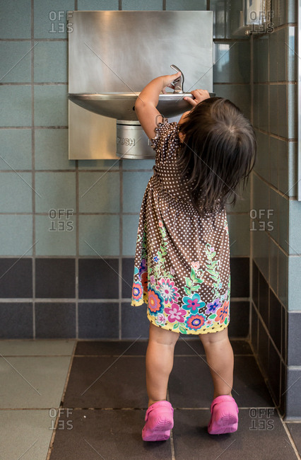 Little girl trying to reach water fountain