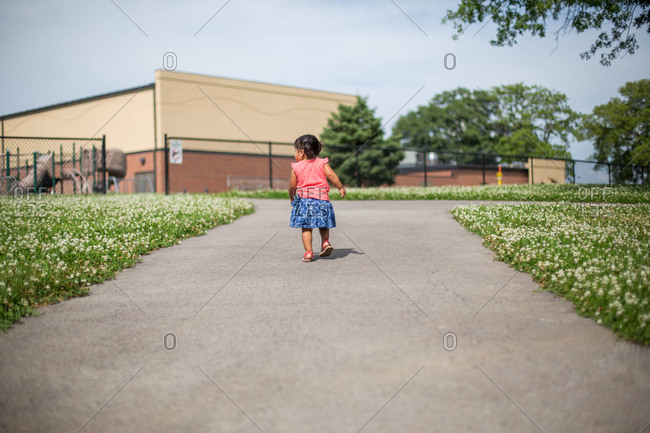 Small girl walking alone on path
