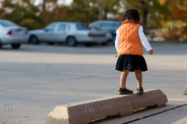 Girl balancing on parking block