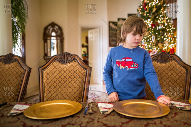 Young boy helping set table for Christmas dinner