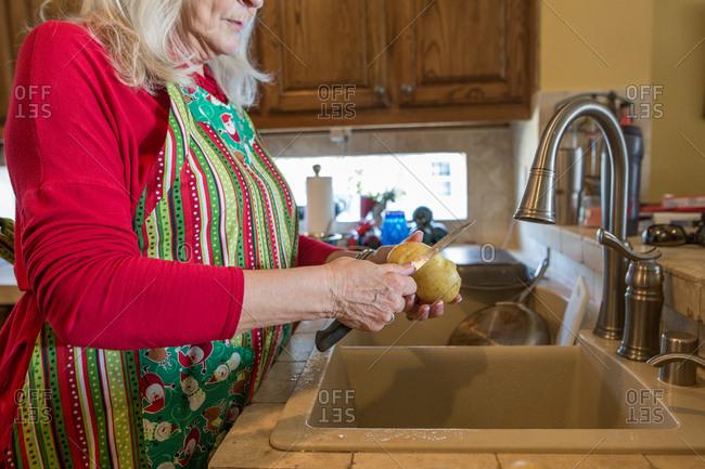 Woman peeling potatoes for family dinner