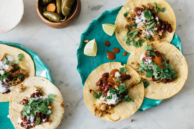 Tacos made with corn tortillas served on plates
