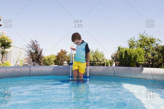 Boy climbing down ladder into swimming pool