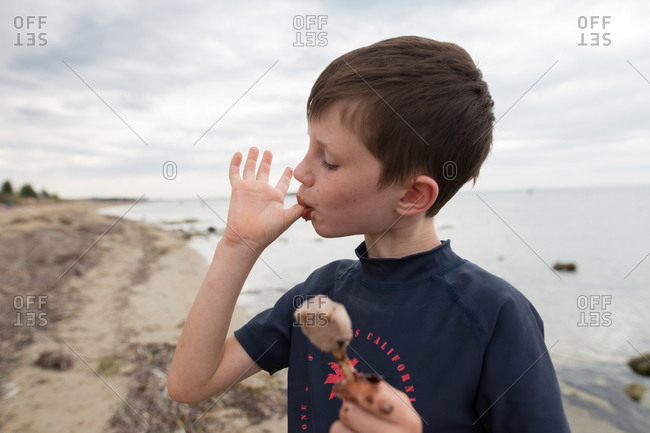 Boy licking his fingers and holding an ice cream bar