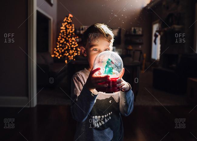 Boy looking at Christmas snow globe
