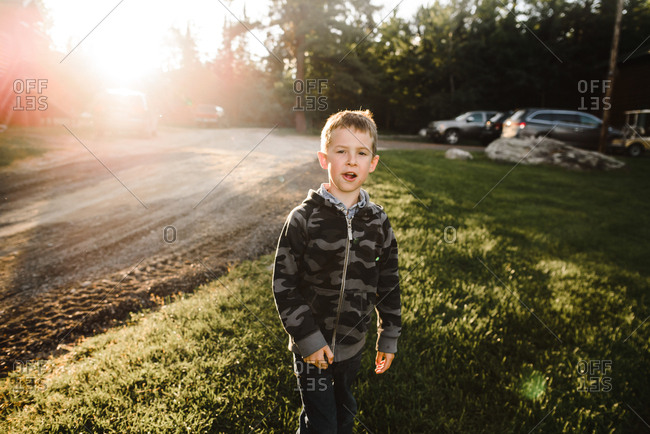 Boy walking outside in grass at sunset
