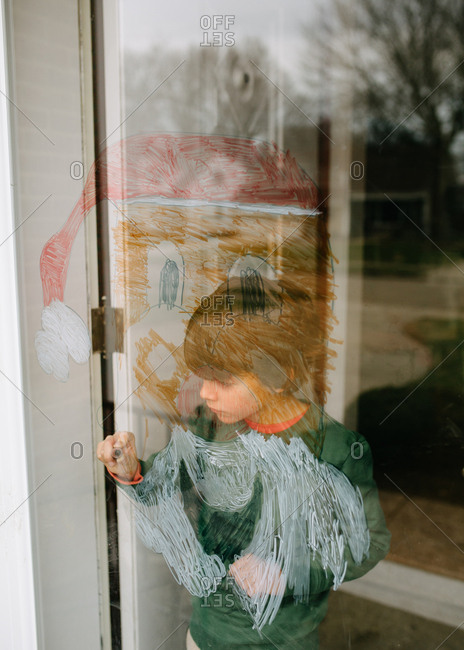 Boy drawing a picture of Santa on a glass door