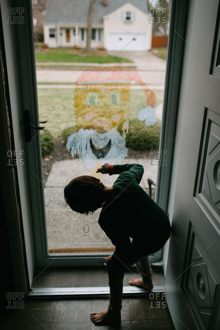 Rear view of a boy drawing a picture of Santa on a glass door