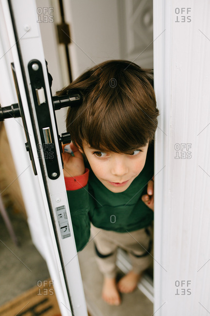 Little boy looking out open door