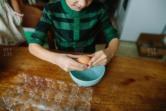 Boy cracking egg into a bowl