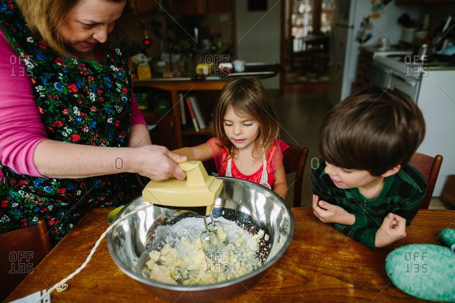 Grandmother and grandkids mixing dough