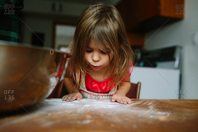 Girl blowing on flour on a wooden table