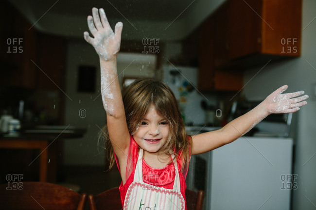 Girl putting flour-covered hands in the air