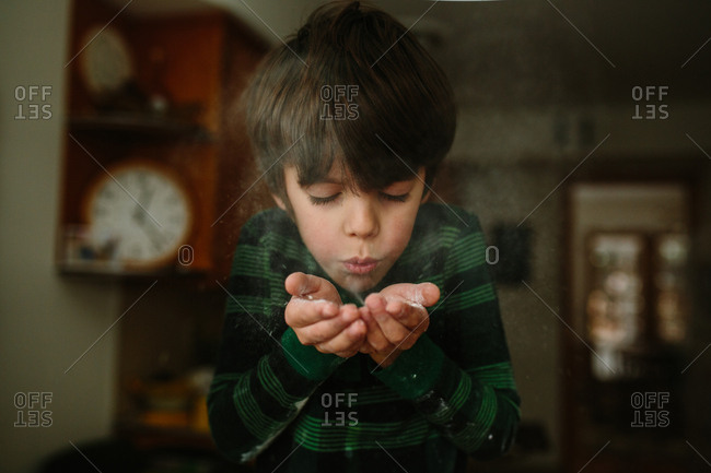 Boy blowing flour from his hands