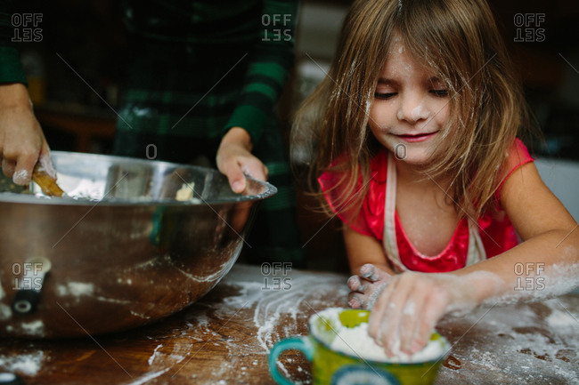 Two kids making cookies in a floury mess