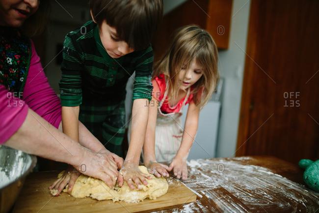 Grandmother and grandkids kneading dough